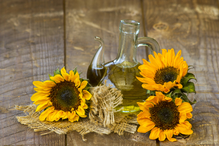 Glass bottle with sunflower oil and sunflowers on wooden background