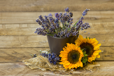 sunflowers and lavender in a vase on wooden background