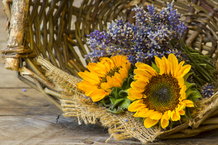 sunflowers and lavender in a basket on wooden background