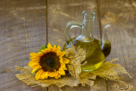 Glass bottle with sunflower oil and sunflower on wooden background