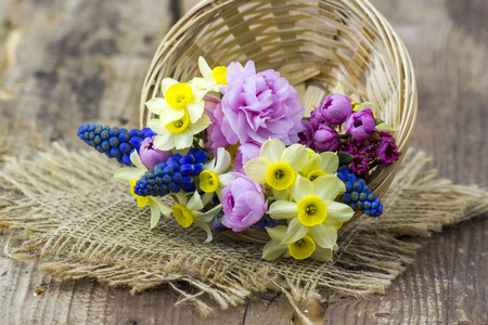 spring flowers bouquet in a basket on wooden background