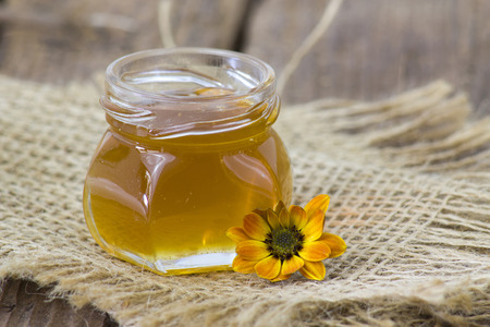 honey and flowers on wooden  background