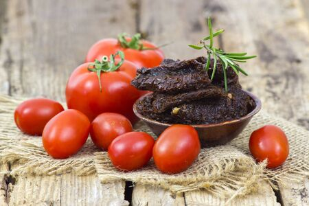 fresh and dried tomatoes on wooden background Stock fotó