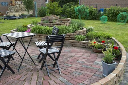 herb spiral in the garden with herbs and flowers