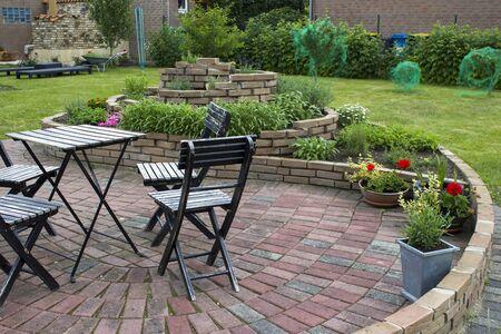 Kräuterspirale im Garten mit Kräutern und Blumen