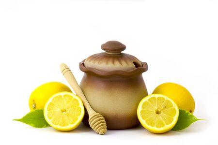 Olla de barro con miel y limones frescos sobre fondo blanco.