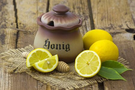 clay pot with honey and fresh lemons on wooden background