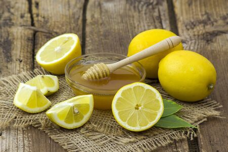 honey and fresh lemons on wooden background