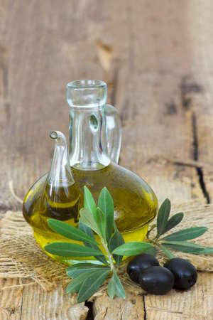 Olive oil and black olives - wooden background 版權商用圖片