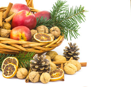 basket full of apples, nuts, cinnamon - white background