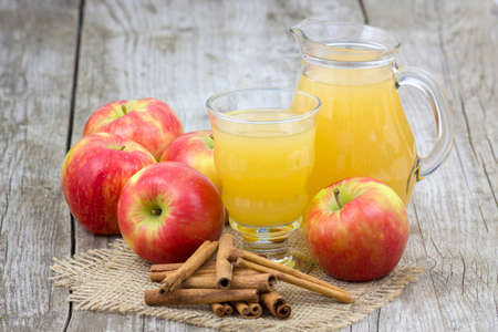 Apple juice and apples on wooden background