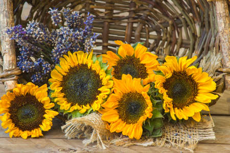 sunflowers and lavender in a basket on wooden background Zdjęcie Seryjne