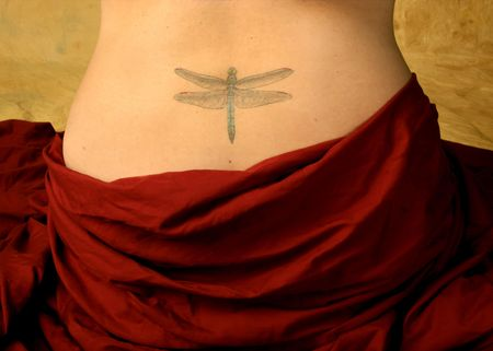 Detail of womans naked back showing dragonfly tatoo with hips covered by red draping