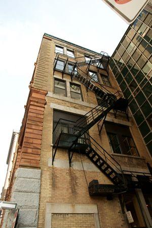 huir: �ngulo de tiro de la parte trasera de un edificio mostrando las escaleras de escape de fuego.