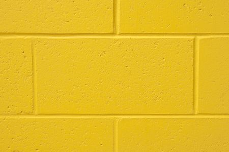solid color: Background of a yellow painted cement wall with copy space Stock Photo