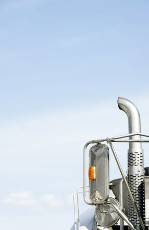 Vertical close-up of a truck's mirors and exhaust pipe against the sky giving copy space, contrast of bright blue sky and pollution source - environmental concept. 스톡 콘텐츠