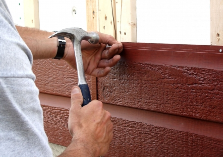 house siding: Action shot of a construction worker hammering a nail to put up new siding during major house renovations.