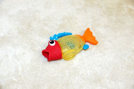 gasping: Concept of fish out of water with colorful plastic toy gasping, trying to breath as it has been thrown out of the tub on the rug by a kid. Stock Photo