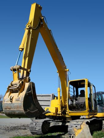 job site: Vertical of mechanical digger in real street urban job site setting contrasted by bright blue sky.