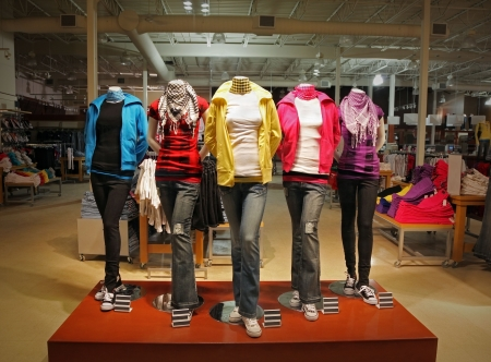 An empty teenage fashion store with five mannequin displaying the latest trend with jeans, hoodies, t-shirts and scarfs. photo