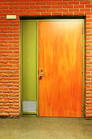 Vertical of a closed wooden door and bricks in a school, room with plate number. Could be office. Nice warm colors.
