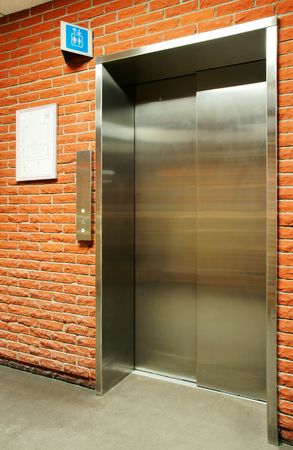Vertical of closed steel door elevator in orange brick wall with blue sign.