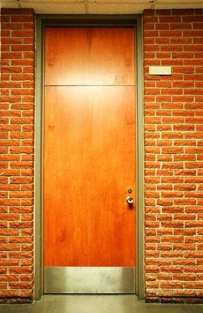 Office building or school wood door in olive green metal frame in terra cotta brick wall.