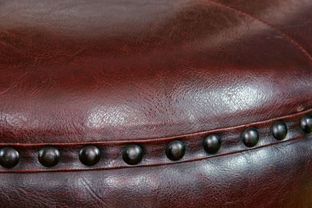 footstool: Nail head beading of deep rich chocolate brown leather round ottoman footstool. Stock Photo