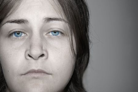 Dramatic faded portrait of a depressed, sad, young woman with stunning eyes. Almost black and white with real color eyes. photo