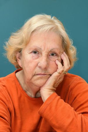 Real senior woman sulking, looking at camera. Much facial details like brown aged spots, wrinkles, no make-up, great color contrast of blue wall and orange shirt. Stock Photo
