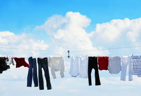 Pants and shirts on clothesline against beautiful white puffy cloud on a sunny day.