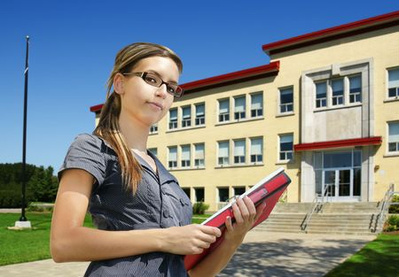 old building facade: Back to school: confident young female student with books in front of school entrance. Could be college or small university campus.