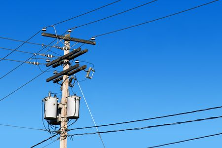 isolator insulator: Energy and technology: electrical post by the road with power line cables, transformers and phone lines against bright blue sky providing copy space.