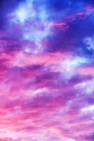 Amazing nature background: dramatic and moody pink, purple and blue cloudy sunset sky shot vertical.