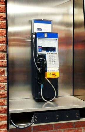 touchtone: Public payphone in stainless steel phone booth on red brick wall. Stock Photo