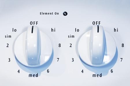 From the kitchen: stove oven burner range white knobs, both OFF. Reklamní fotografie