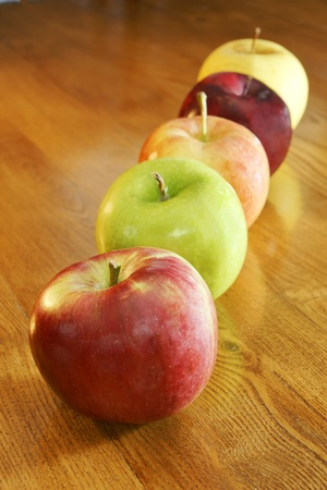 Apples of all kinds in a row on a kitchen wooden table: cortland, granny smith, gala, red and golden delicious.