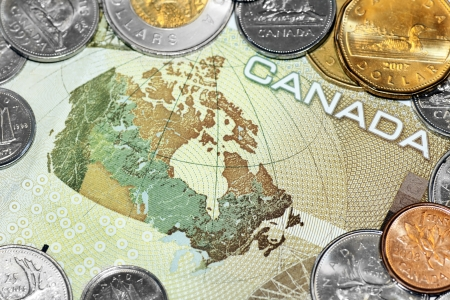 Close up of a one hundred canadian dollar bill showing the map of Canada, surrounded by loony and tuney coins. photo