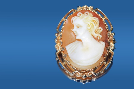 cameo: Fine jewelry: beautiful antique cameo on blue reflective background.