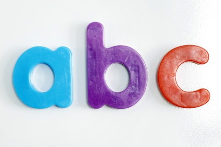 Fridge magnet: colorful plastic alphabet letters on textured white refrigerator.