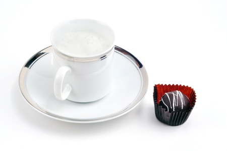 indulgence: Afternoon indulgence: capucino coffee or latte served in fancy gold trim cup and saucer with chocolate. Stock Photo