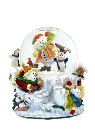 Musical snowglobe with snowmen and penguins enjoying winter. photo