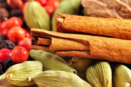 Food background: variety of whole spices for a recipe, cinnamon sticks, cardamons, pink peppers and nutmeg. photo