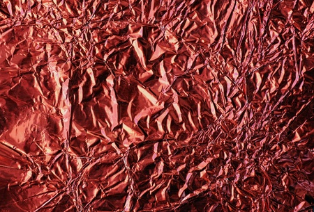 Great metallic background with many details: macro of crinkled red aluminum foil wrapping paper. Stock Photo