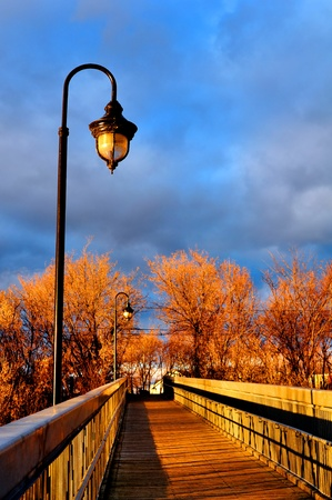 Sun setting over the wooden bridge of a small town on a autumn day.