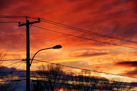 Sun setting over the electricity post and cables of a small town. Stock Photo - 9225344