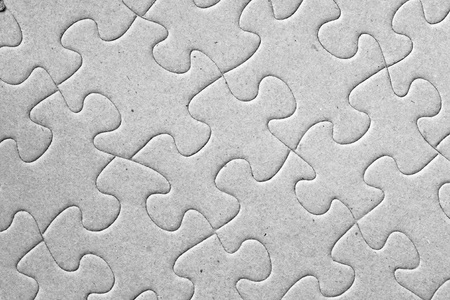 Blank grey complete cardboard jigsaw puzzle shot at an angle, great details on the pieces