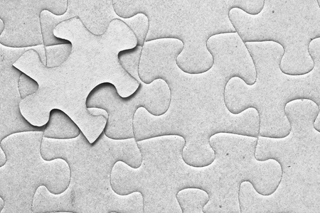 Complete grey cardboard jigsaw puzzle with one floating piece on top photo