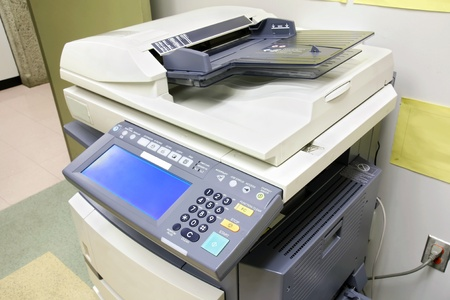 photocopier: Modern photocopier with digital display plugged to the wall in the office supply room. Stock Photo