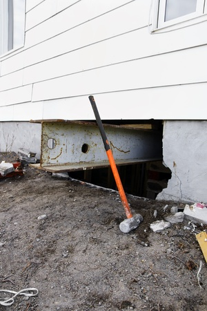 Major reno: sledgehammer against strong steel beam inserted for support to lift and old house with white siding to change the damaged concrete block foundation. photo